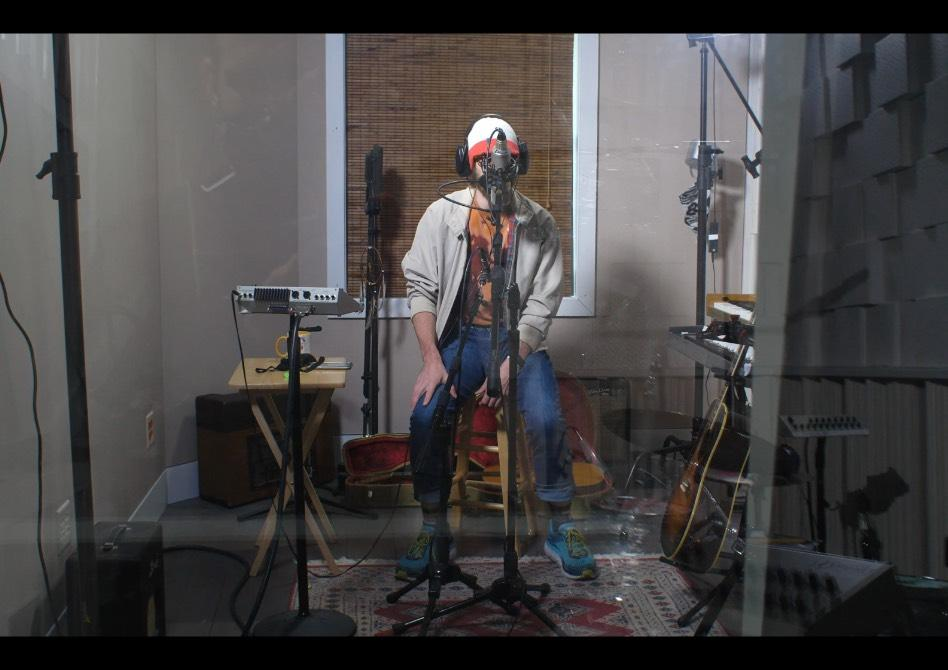 A musician singing into a microphone at Trace Horse studios